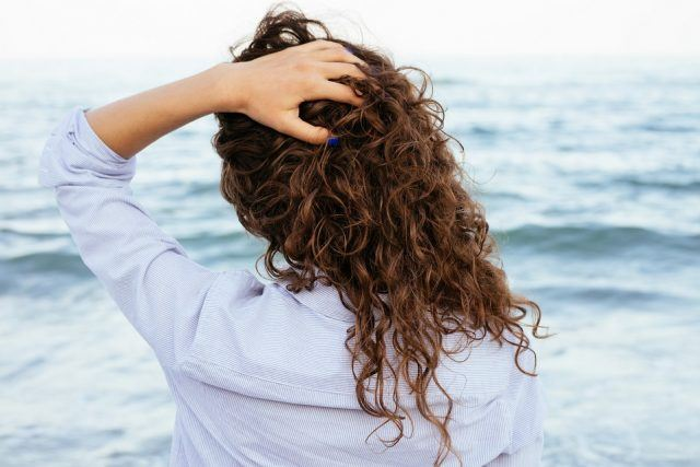 woman in shirt looking at the sea and keeps her hair