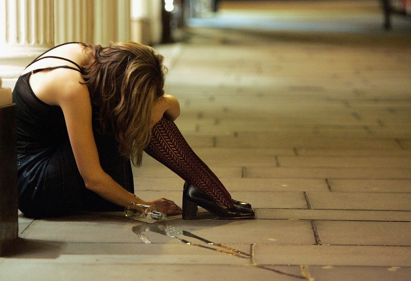 A woman, possibly fighting addiction, slumped over in front of a club