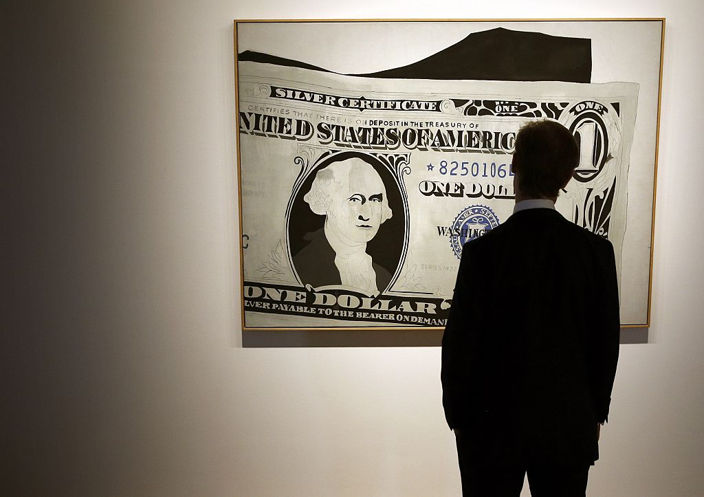 """A Sotheby's employee poses with a piece of artwork entitled """"Silver Certificate, 1962,"""" an acrylic on canvas by US artist Andy Warhol"""