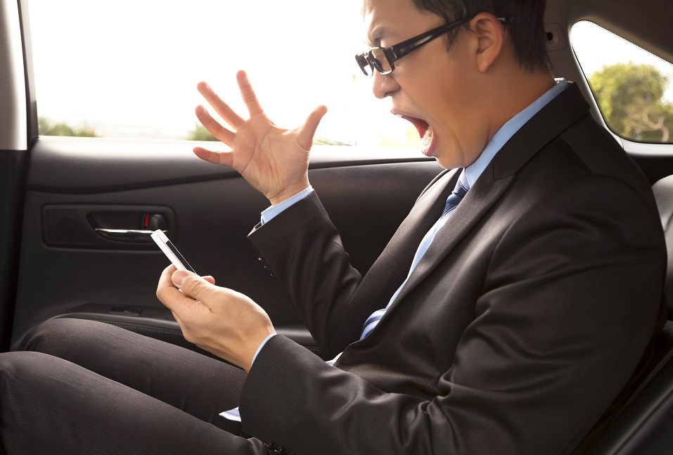 A businessman shouts at his phone while gesturing in the passenger's seat of a car