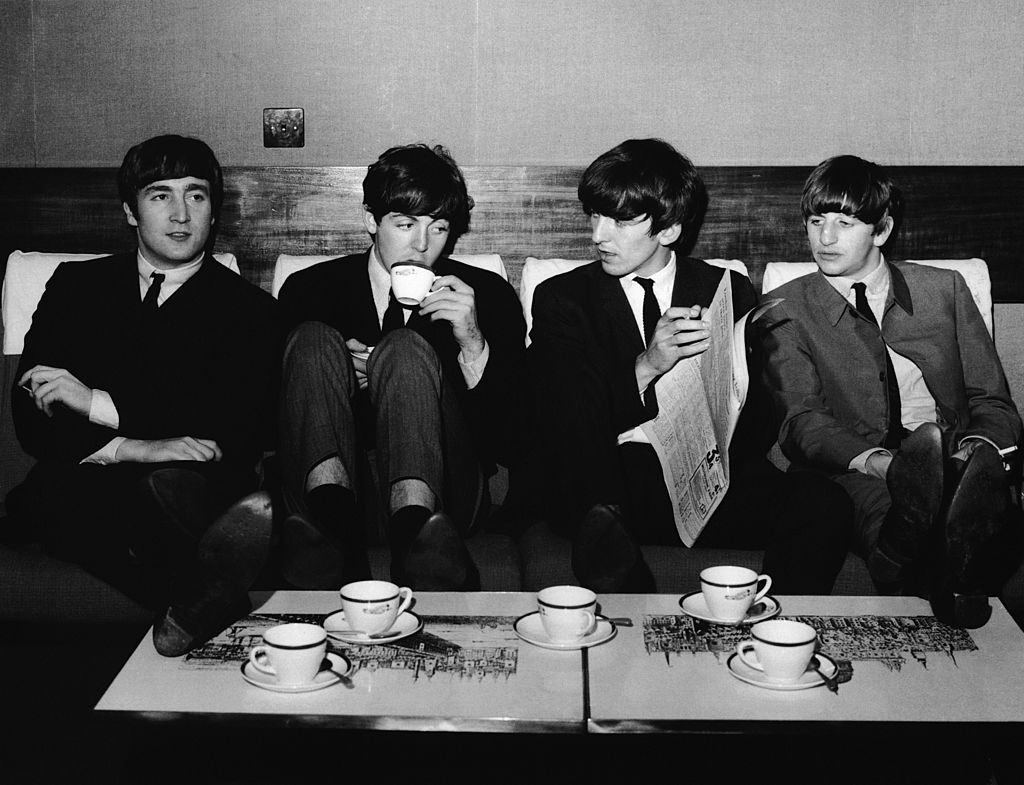 the beatles sitting and drinking coffee.
