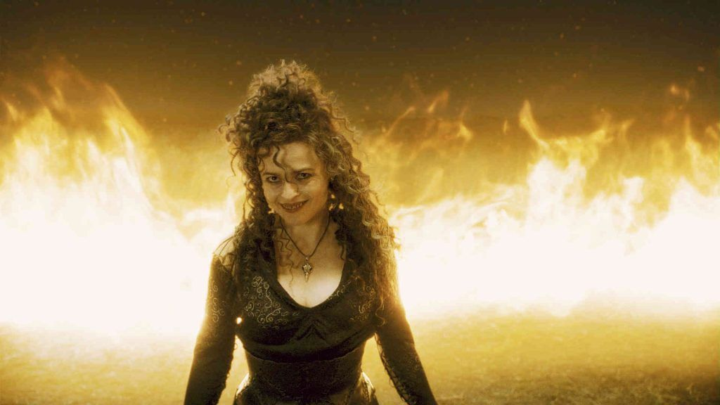 Helena Bonham Carter as Bellatrix Lestrange smiling with a ring of fire behind her in Harry Potter and the Half-Blood Prince