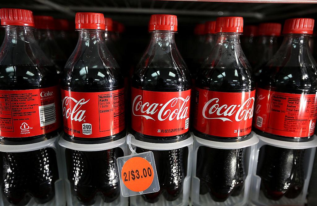 Bottles of Coca-Cola sit in a cooler