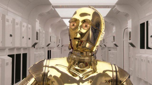 C-3PO looks towards the right in a white room