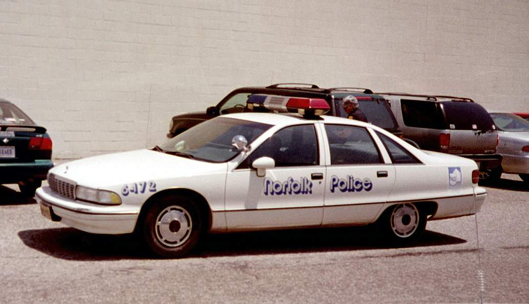 White Chevrolet Caprice American cop car in a parking lot.