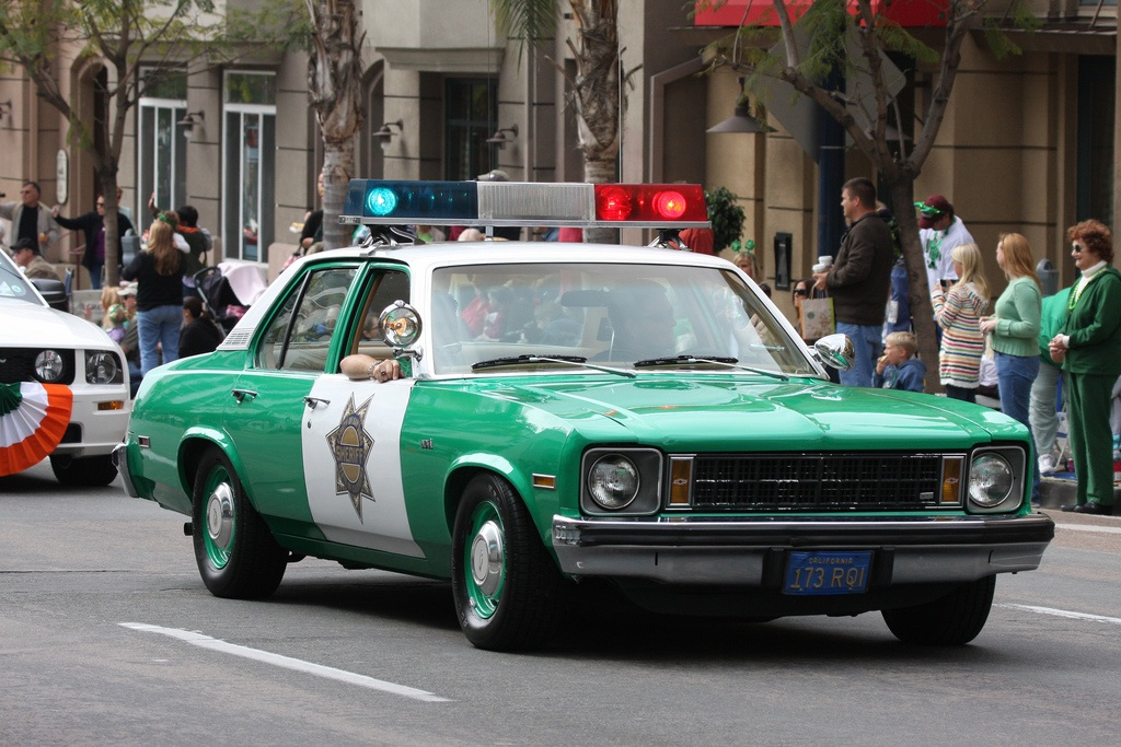 Green and white Chevrolet Nova cop car