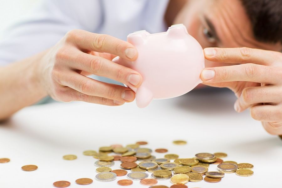 businessman pouring coins from piggy bank