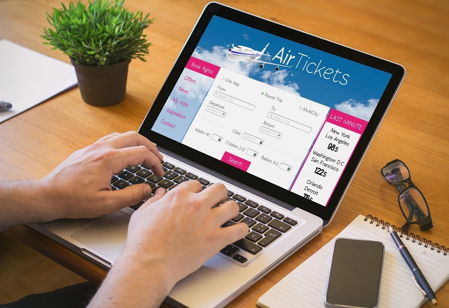 man working on laptop with tickets fligths web