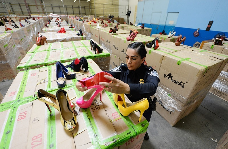 A U.S. Customs and Border Protection officer displays counterfeit designer shoes