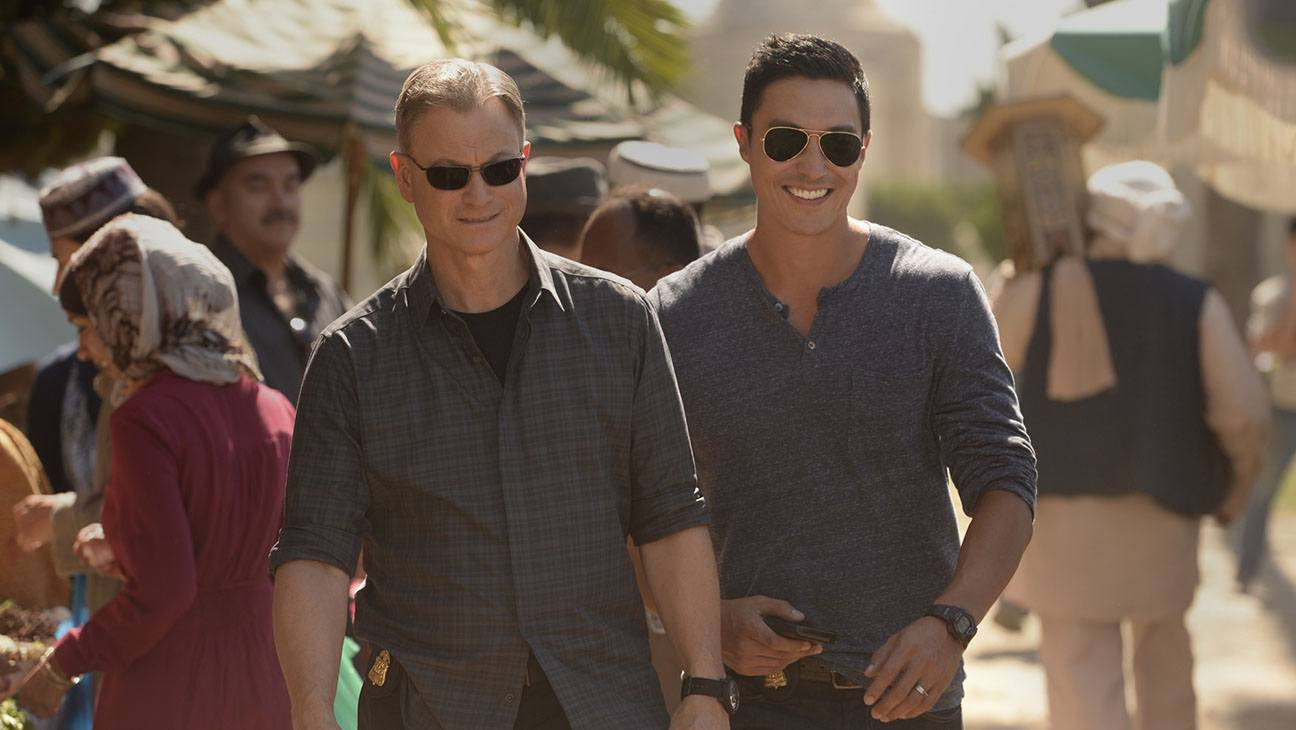 Gary Sinise and Daniel Henney walk in a busy marketplace in a scene from Criminal Minds: Beyond Borders