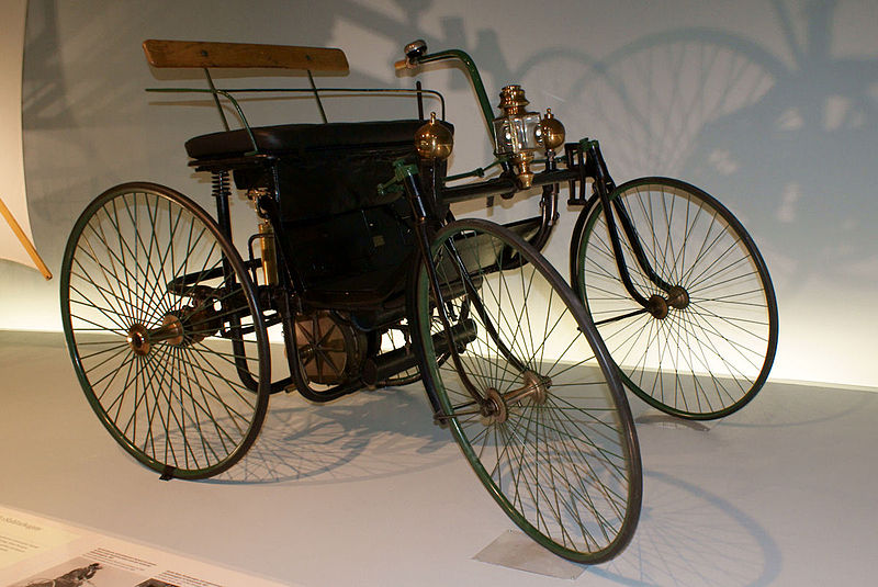 One of the oldest cars in the world, the Daimler-Maybach Stahlradwagen, in a display case in a museum.