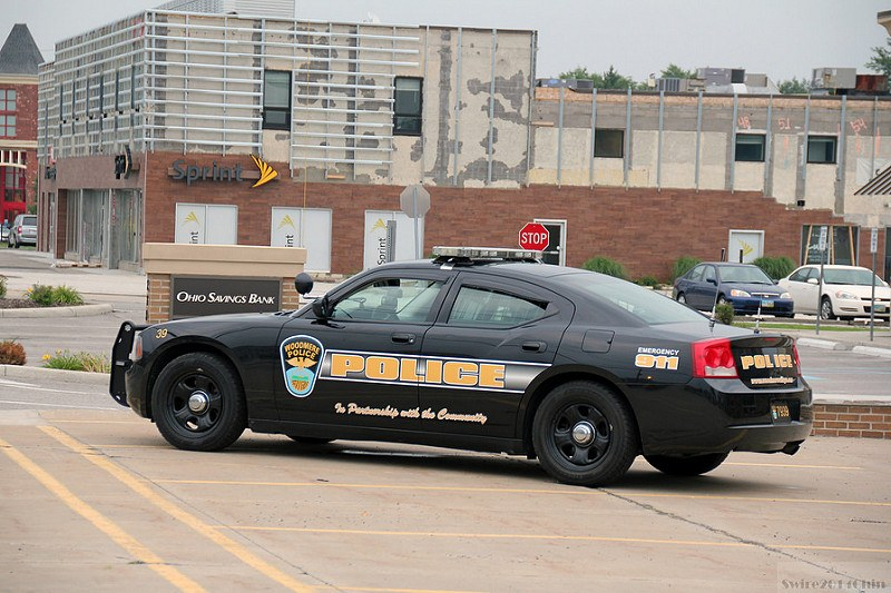 A Dodge Charger cop car parked at a bank.