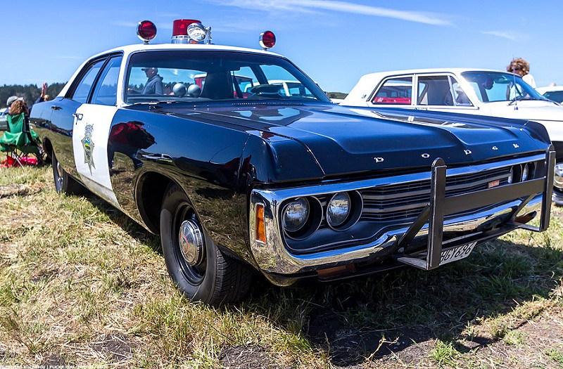 A Dodge Polara cop car parked on grass.