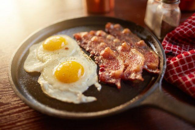 Bacon and eggs in iron skillet.