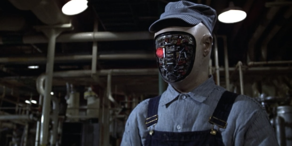 A robot with an exposed mechanical face stands in a warehouse.