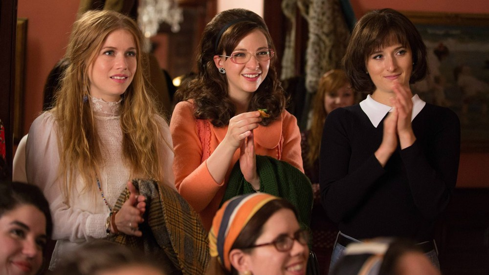 A group of women sit on a podium and clap in their hands in Amazon's Good Girls Revolt