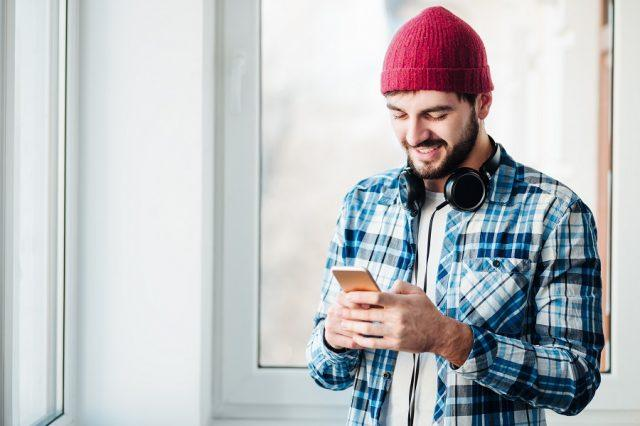 guy using a smartphone to listen to music with headphones