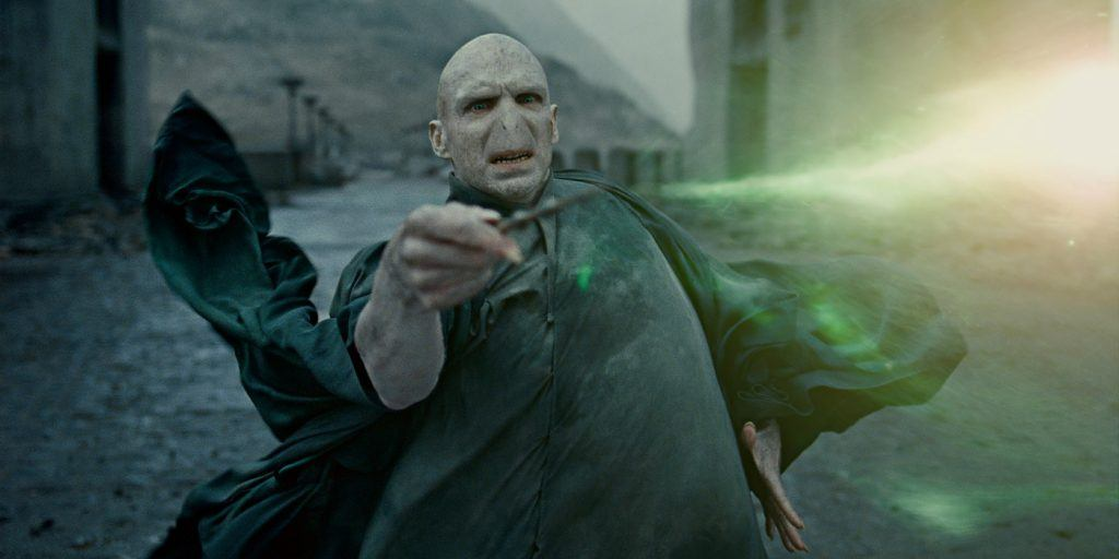 Voldemort casting a spell with his wand as green light shoots out of it