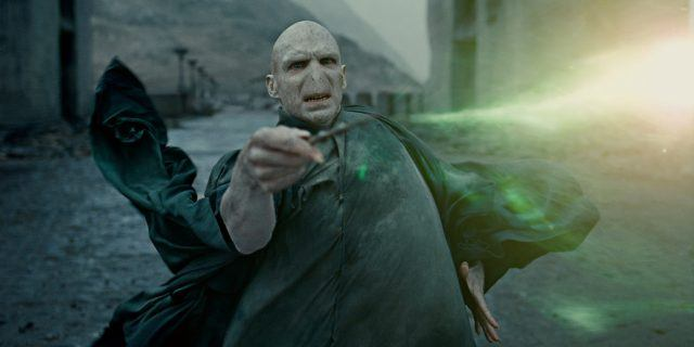 Voldemort casting a spell with his wand as green light shoots out of it.