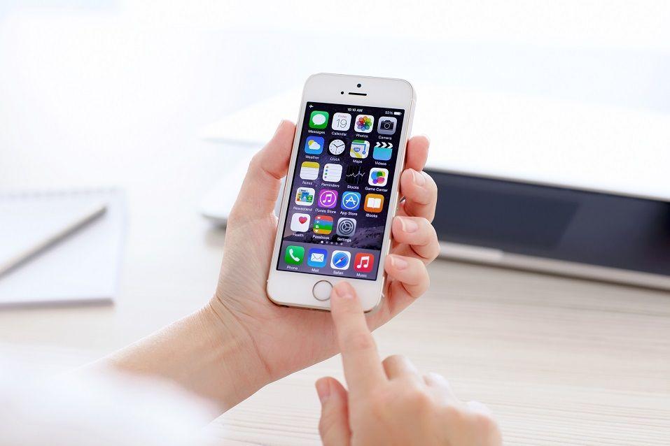 Apple iPhone 5S displaying iOS 8 homescreen