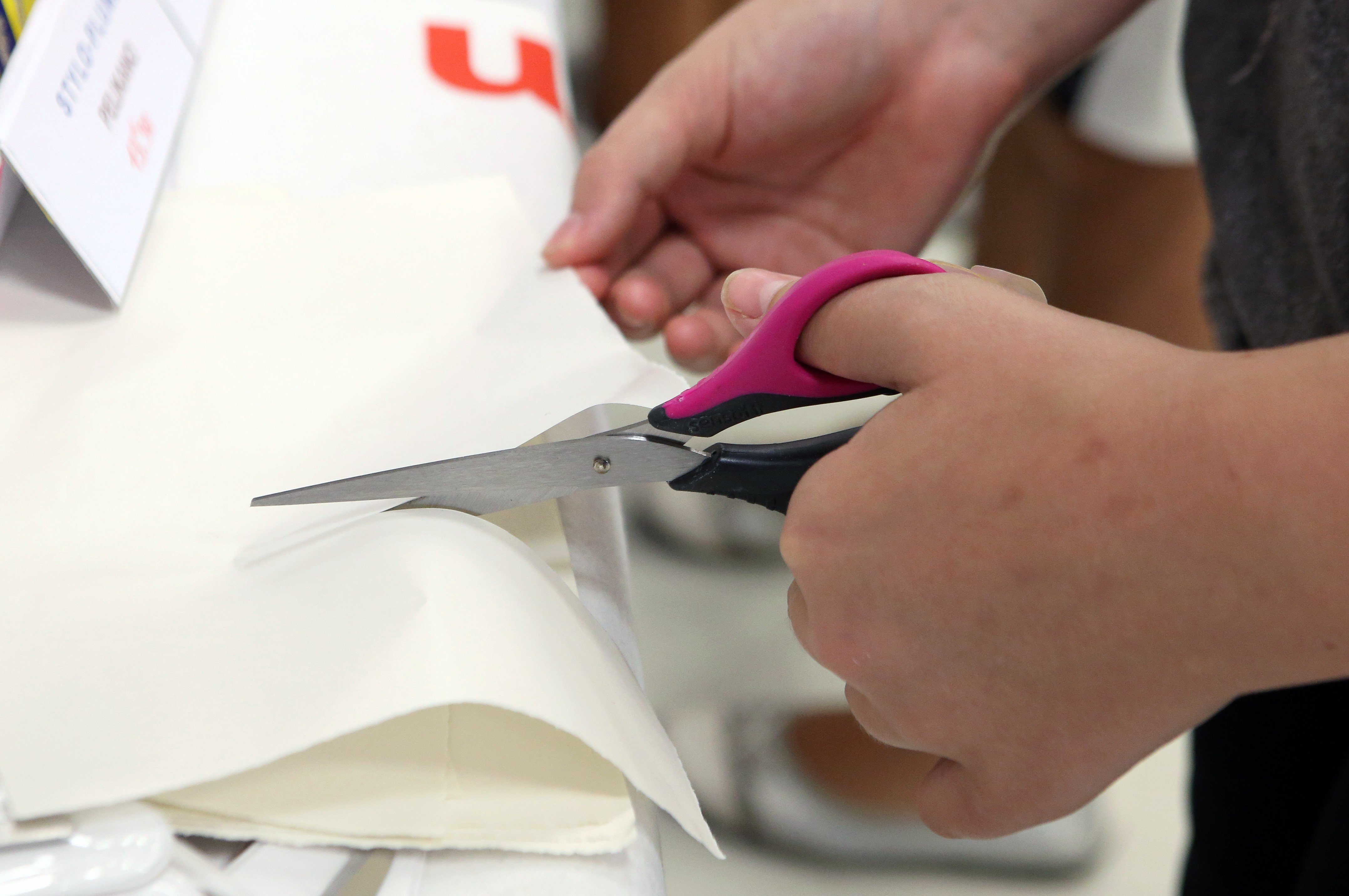 A person cuts paper with scissors for left-handed users