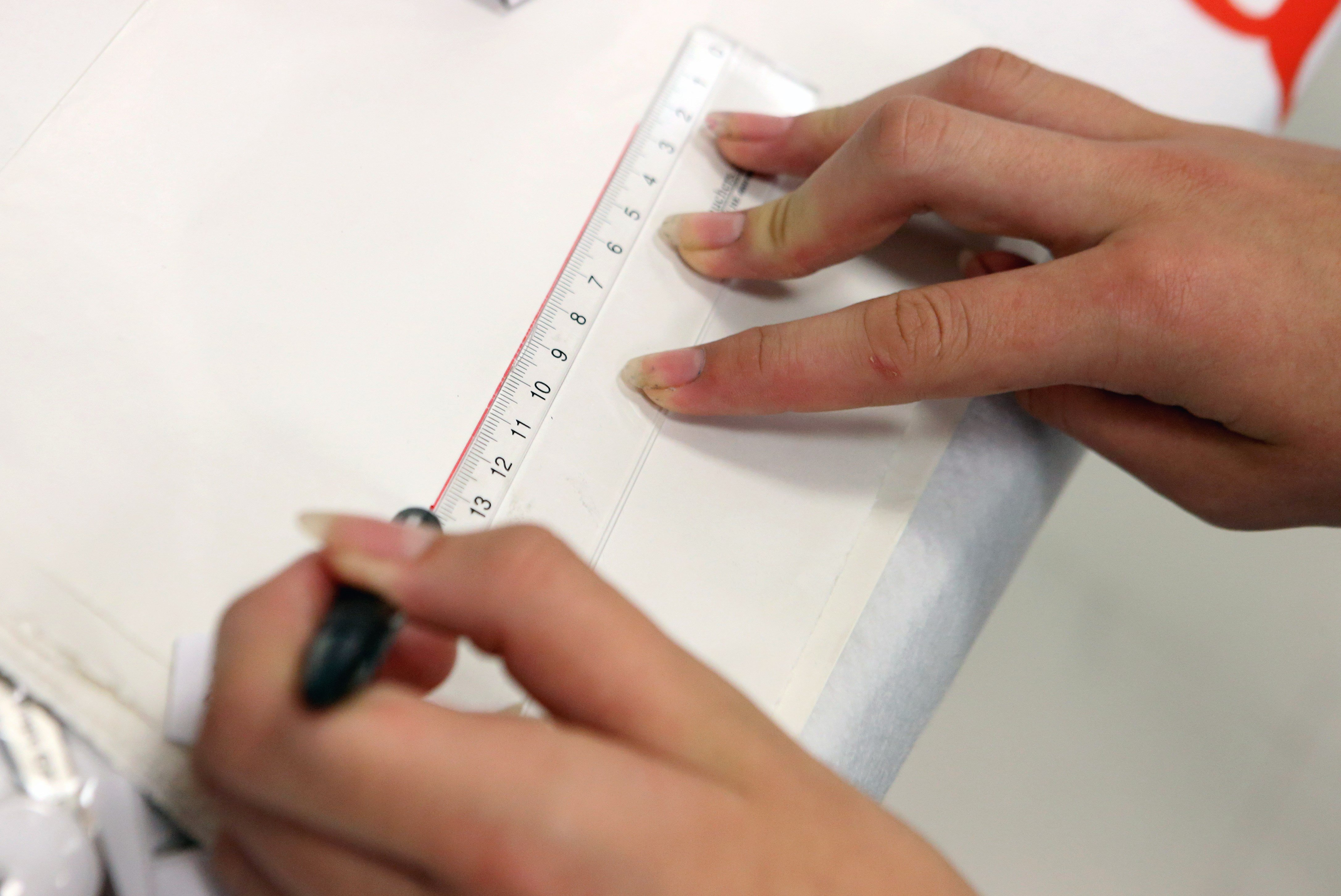 A person uses a special ruler for lefties at work