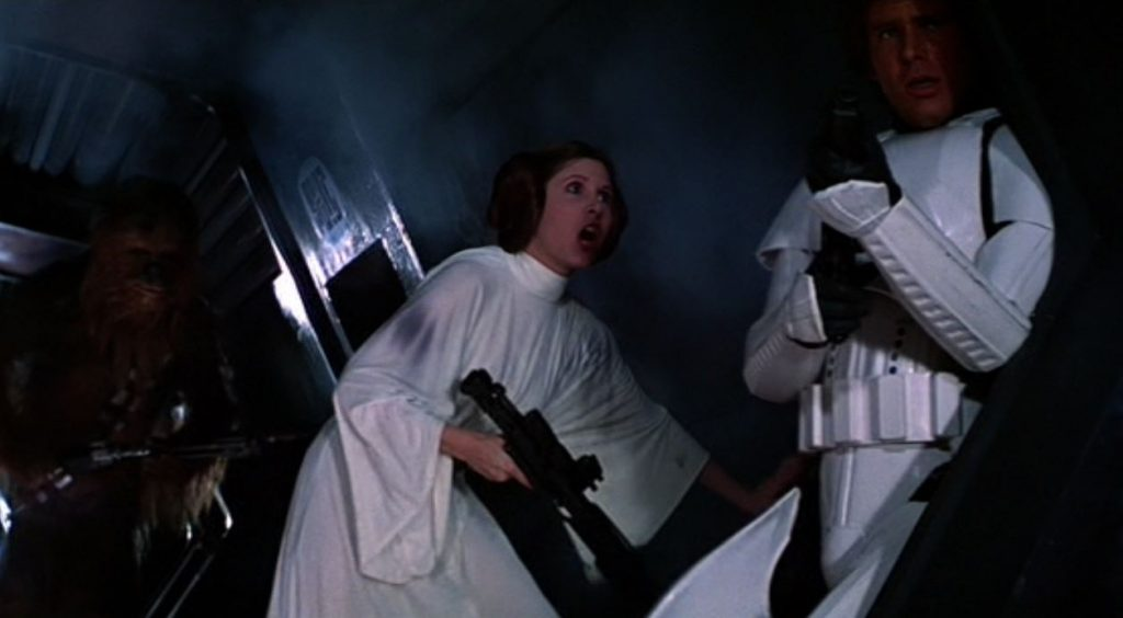 Princess Leia is holding a gun and talking to Han Solo in a hallway in Star Wars: A New Hope