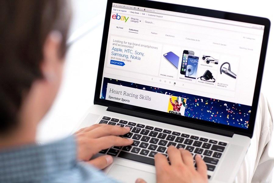 man accessing eBay on laptop