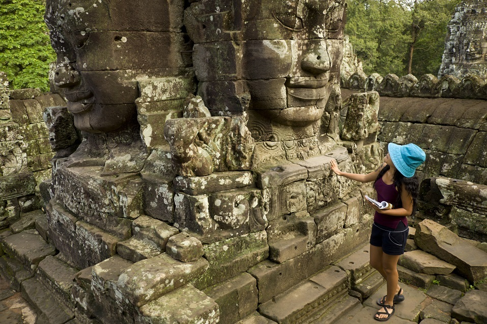 young visitor meets giant stone heads at the top terrace of the Bayon, at Angkor Thom, Cambodia