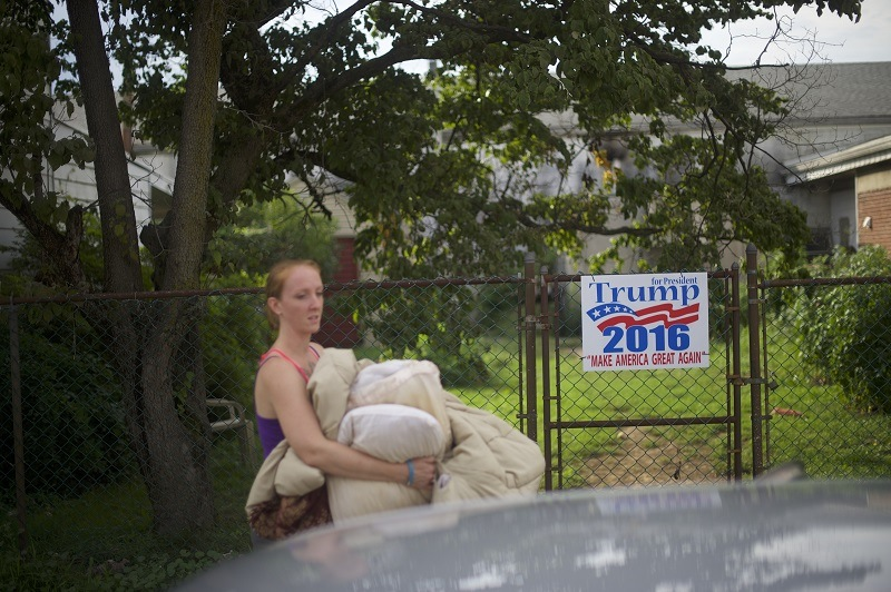 A middle class woman passes by Trump sign as she packs up her car in rural Pennsylvania