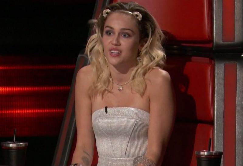 Miley Cyrus sits in a coach's chair on The Voice