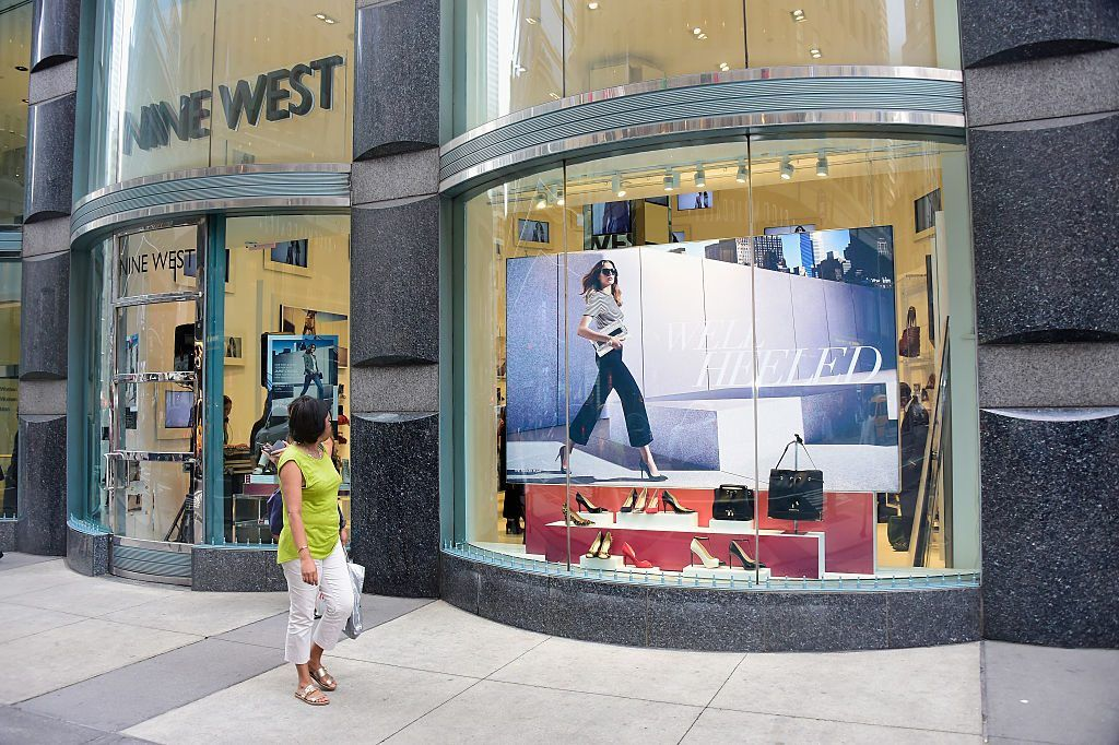 A woman looks at a Nine West storefront