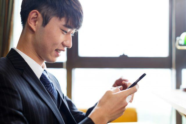 handsome man playing with smartphone