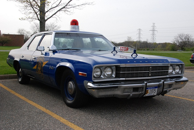 Blue Plymouth Fury cop car parked in a parking lot.