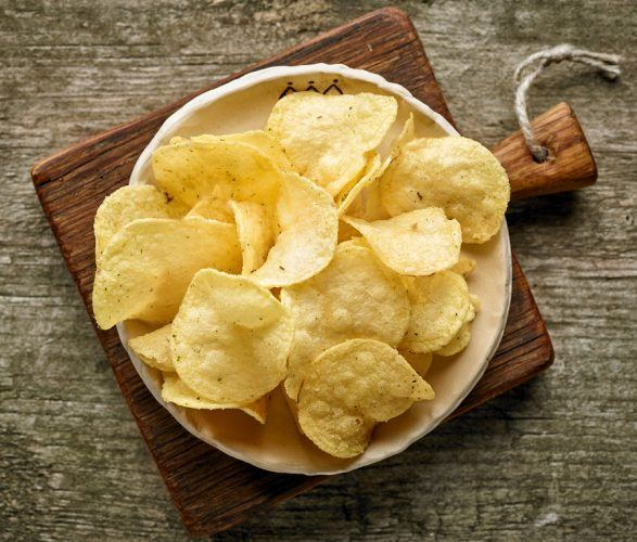 Bowl filled with potato chips sitting on wooden table.