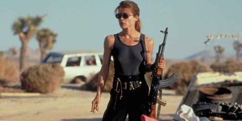 Woman in a tank top and sunglasses holding a rifle in the desert
