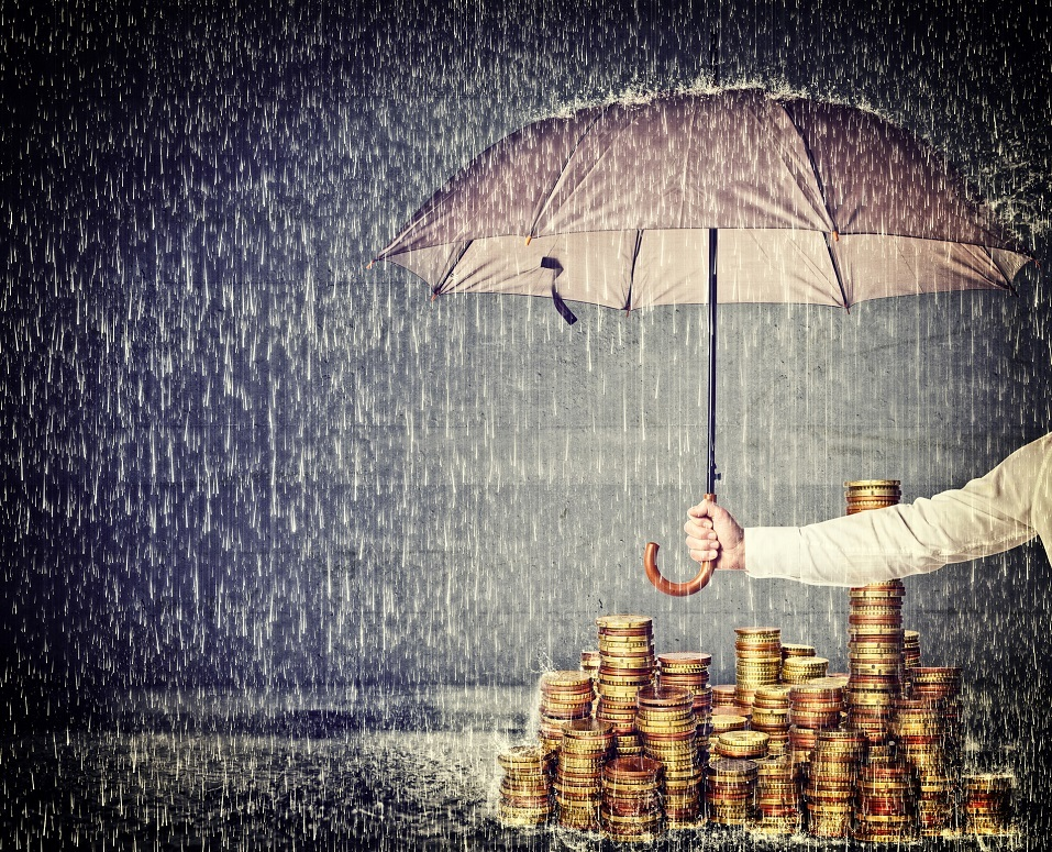 An umbrella protecting golden coins from the rain
