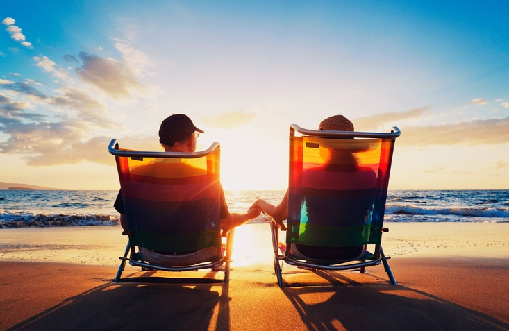 senior couple sitting on beach at sunset