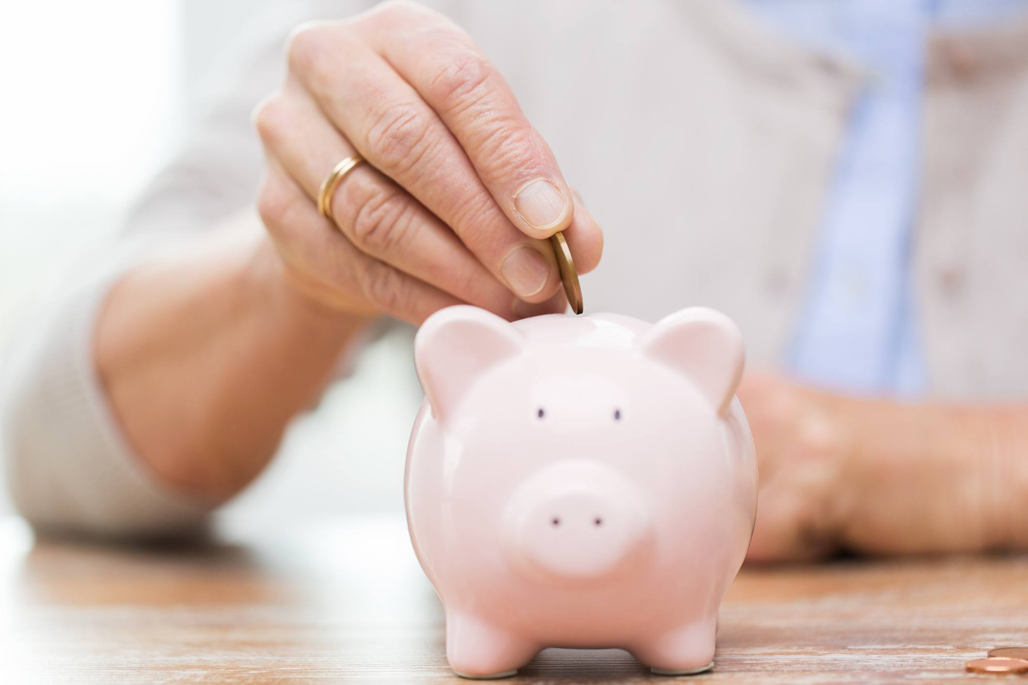 woman hand putting coin into piggy bank
