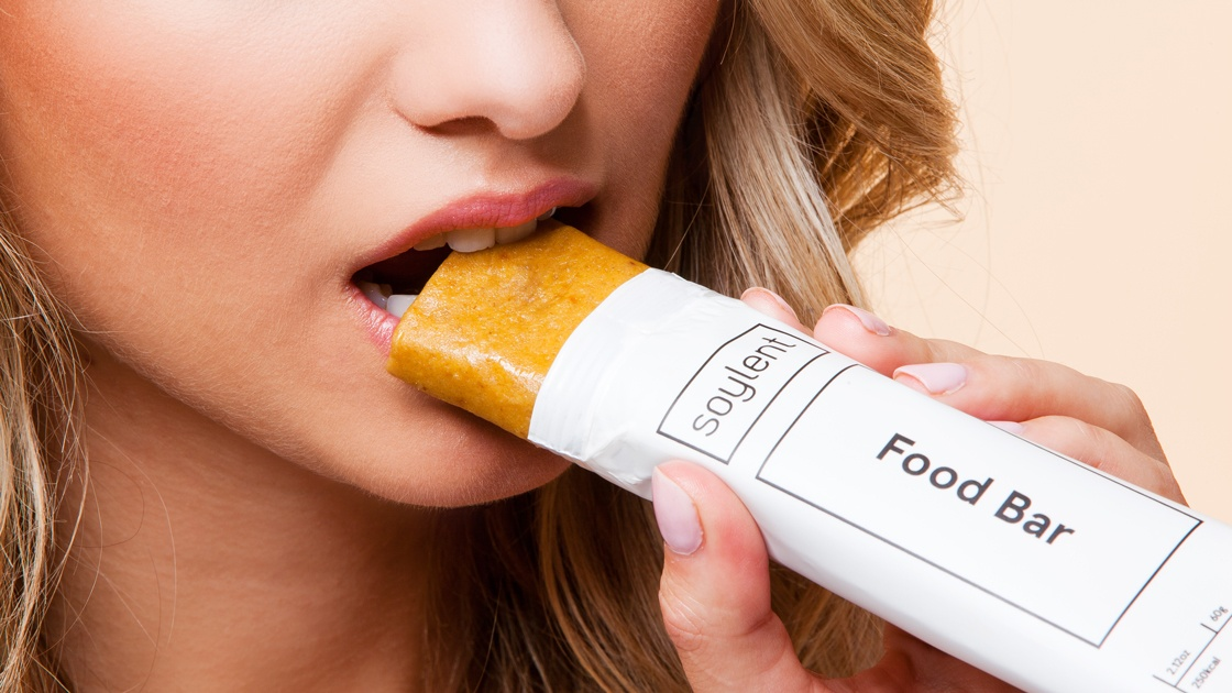 A woman eating a Soylent Food Bar