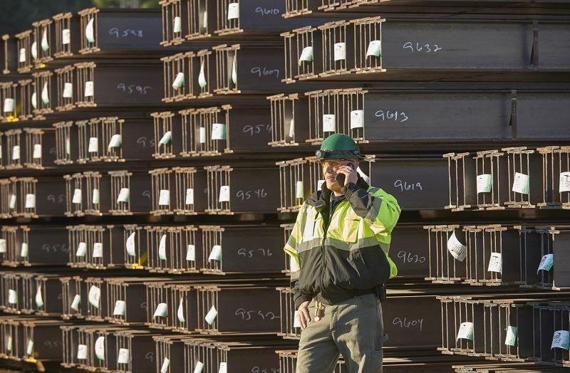 Man communicating near steel beam in a shipping yard