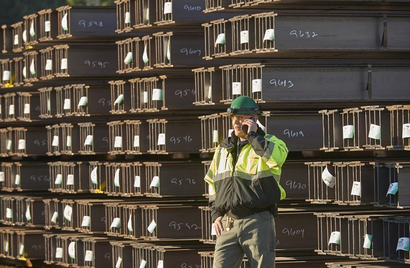 Worker near steel beams in shipping yard