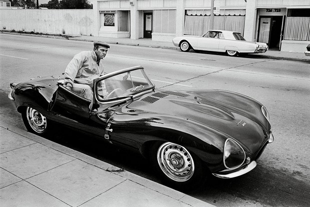 A black and white photograph of Steven McQueen in a 1956 Jaguar XKSS