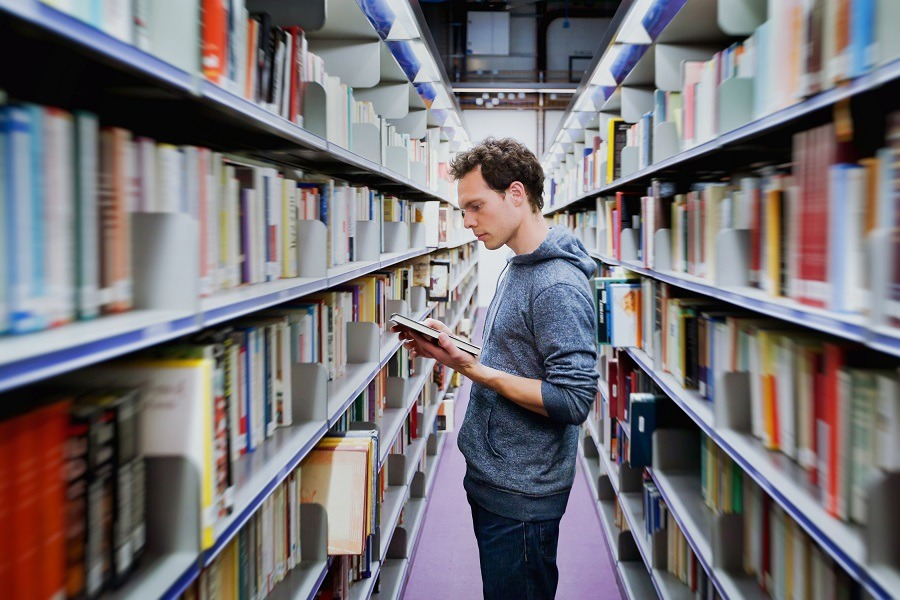 Young man reading a book in between library shelves