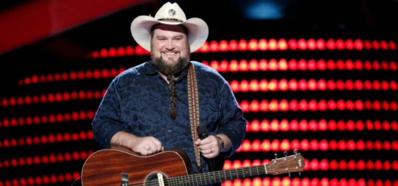 Sundance Head is holding is guitar and smiling on the stage of The Voice.
