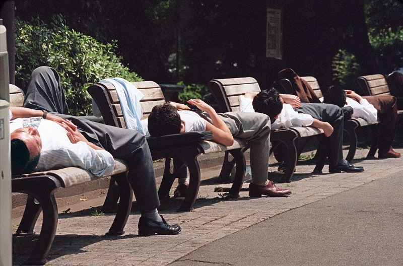 Japanese businessmen take naps on benches in Tokyo