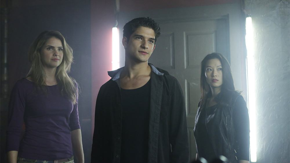Tyler Posey stands with a group in front of a door in Season 4 of Teen Wolf