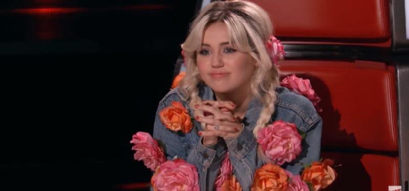 Miley Cyrus is wearing a denim jacket with flowers on it on The Voice.