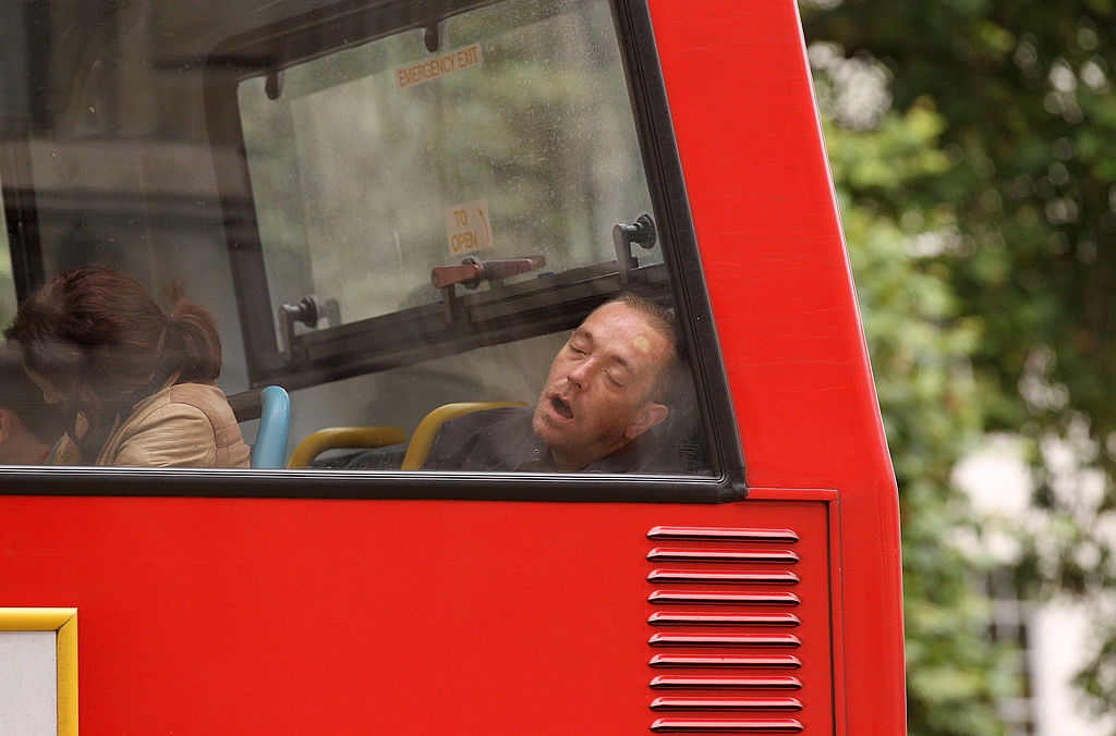 A man sleeps as he rides the bus in London, England