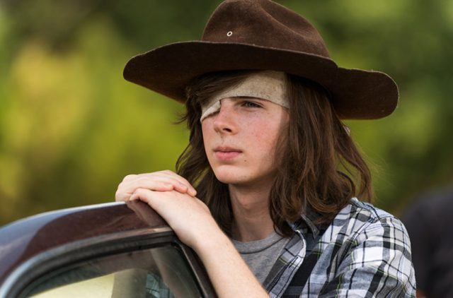 Carl is leaning on a car door with his eye patch and hat.